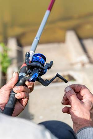 Male hand with a spinning rod in his hands. The concept of fishing