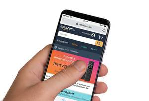 Male hands holding smartphone with an open Amazon website