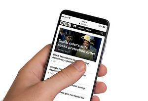 Male hands holding smartphone with an open BBC News application