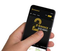 Male hands holding smartphone with an open Binance application
