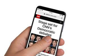 Male hands holding smartphone with an open CNN website