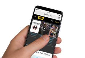 Male hands holding smartphone with an open IMDb website