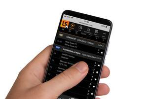 Male hands holding smartphone with an open Livescore application