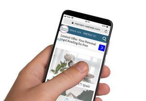 Male hands holding smartphone with an open Merriam Webster website