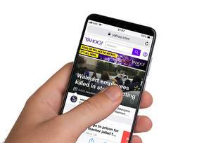 Male hands holding smartphone with an open Yahoo! website