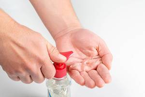 Male hands squeeze an antiseptic into his hands, close-up