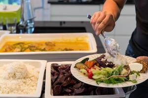 Man at buffet stand scoops white rice on a a healthy dinner plate with salad, vegetables and sliced beetroot