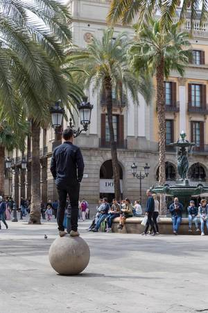 Man balancing on a stone ball under palm trees, next to  fountain of the Three Graces and helmet lamps designed by Antoni Gaudi in Barcelona, Spain
