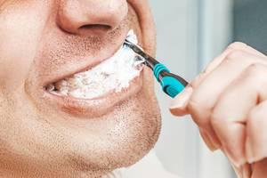 Man brushing his teeth in bathroom (Flip 2019)