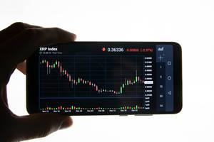 Man checking Ripple price graph chart on mobile phone screen