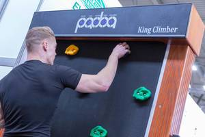 Man climbs the King Climber at Fibo fitness trade show while details like time and speed of climbing are shown at the top
