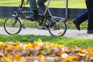 Man cycling in a park with folding bike, sui trousers and house slippers