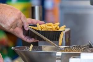 Man filling a plastic box with french fries