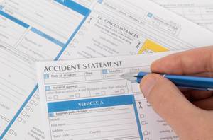 Man filling out accident statement report