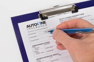 Man filling out car insurance policy