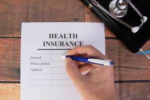 Man filling out health insurance form