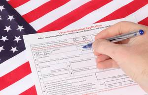 Man filling out Voter Registration Application with USA flag in background.jpg