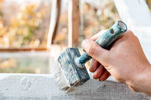 Man hand paints wooden surface with white paint