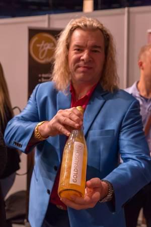 Man holding a bottle of Goldrausch golden water