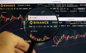 Man holding magnifying glass over Binance logo