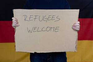 Man holding refugees welcome sign