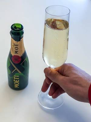 Man holds a glass of champagne next to an empty Mini Moët bottle on a white background
