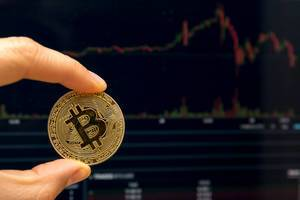 Man holds a golden bitcoin between his fingers in front of stock market picture