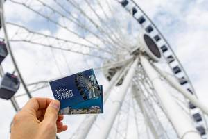 Man holds Navy Pier tickets in his hand, with a big Ferris wheel in the background