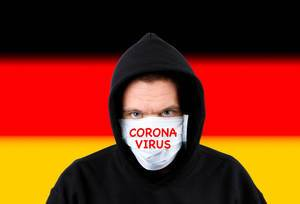 Man in hoodie wearing protection face mask with flag of Germany