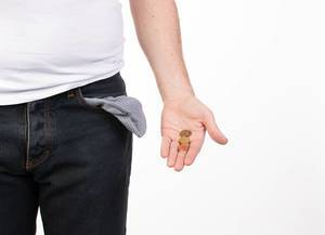 Man in jeans with empty pocket holding coins