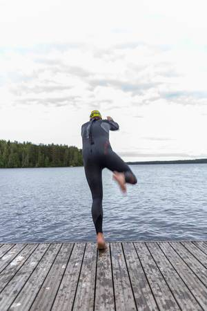Man in swim gear is about to take a header into the lake Päijänne to cool off and go swimming