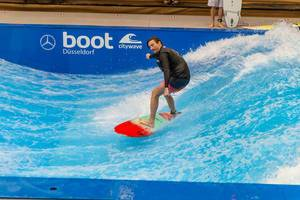 Man is surfing on citywave - standing wave at the exhibition boot Dusseldorf, Germany