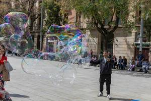 Man makes giant colourful soap bubbles in the city center of Barcelona