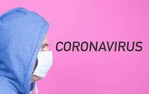 Man mit Pullover trägt eine Gesichtsmaske und schaut auf das Wort Coronavirus auf pinkem Hintergrund