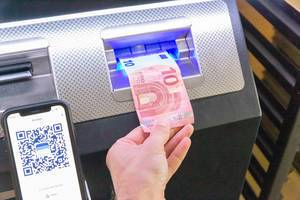 Man puts 10 Euro in a Bitcoin ATM, to transfer Bitcoins to his Smartphone via BlueWallet App
