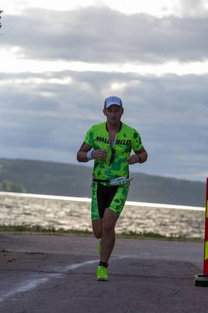 Man runs the marathon as part of the triathlon competition Ironman 70.3 on the coast of Lahti, Finland