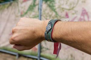 Man shows the Tomorrowland festival bracelet on his hand with the logo of the festival on it