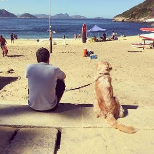 Man sitting next to his Dog facing the Beach in Rio De Janeiro