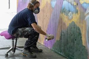 Man sitting on a chair and spraying graffiti