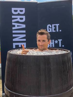 Man takes an ice bath in an old wooden barrel to regenerate himself after hard training and sports