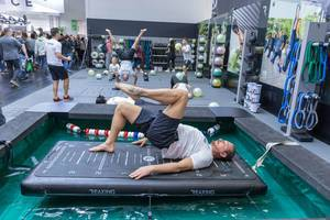 Man traint at a ReaxBoard and presents a new innovative way of neuromuscular training at Fibo fitness trade show in Cologne