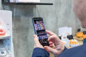 Man uses his smartphone to take a photo of multicoloured donuts on display at the Anuga food fair in Cologne, Germany