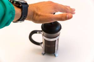 Man using the French Press to make coffee