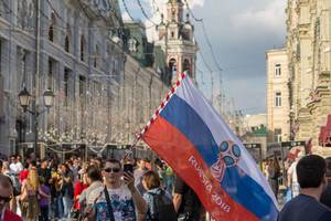 Man waving a Russian flag and recording with his phone