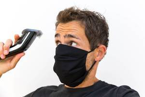 Man with black face mask cuts his own hair at home with a Philips QC5115/15 hair clipper