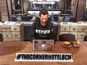 Man working on his Macbook with stickers, next to a coffee in the Corner Hotel Lounge, behind a #TheCornerHotelBCN Hashtag banner