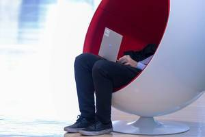 Man working on laptop in designer-chair