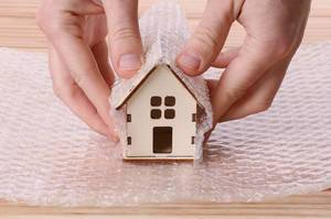 Man wrapping house in bubble wrap