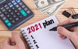 Man writing 2021 plans in notebook