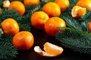 Mandarinen mit Tannenzweigen auf schwarzem Hintergrund